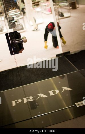 Worker Cleaning Prada Store in Fifth Avenue at night, Manhattan, New York City, New York State, USA - Stock Photo