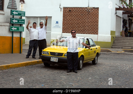 Friendly taxi cab drivers in Puerto Vallarta, Mexico, standing by a taxi cab ready to take tourists to their destination. - Stock Photo