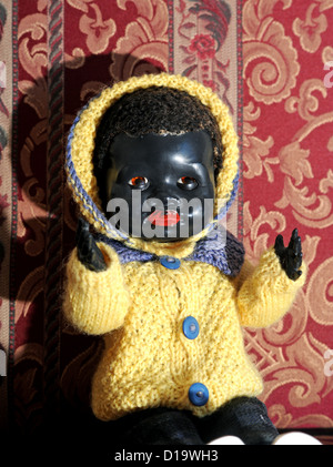 Antique black baby china toy doll in a chair - Stock Photo