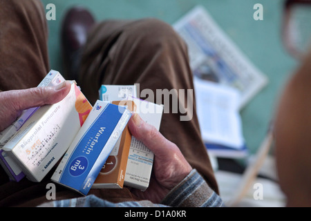 Elderly old aging man's hands holding medication tablets, heart, pain relief, at in home, England UK - Stock Photo