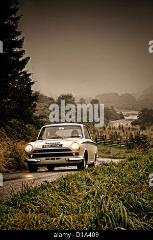 1965 Ford Lotus Cortina driving on a country road in Northumberland UK - Stock Photo