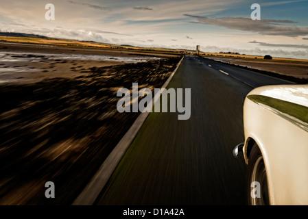 1965 Lotus Cortina driving across the Holy Island causeway in Northumberland - Stock Photo