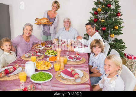 Mother bringing turkey to dinner table - Stock Photo