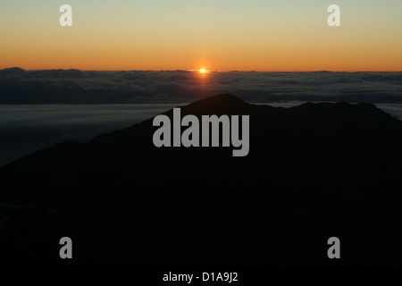 Day break and sunrise over the clouds from Haleakala volcano, Maui, Hawaii - Stock Photo