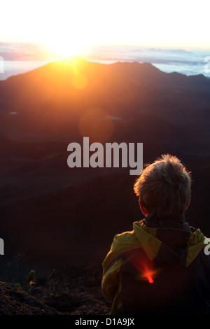 Boy taking in the sunrise at Haleakala, Maui, Hawaii - Stock Photo