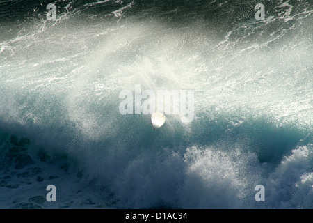 Giant wave spitting out surfboard after surfer wipe out, maui, hawaii - Stock Photo