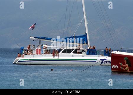Tourists on catamarans and snorkelers in Honolua Bay, Maui Island, Hawaii, USA - Stock Photo
