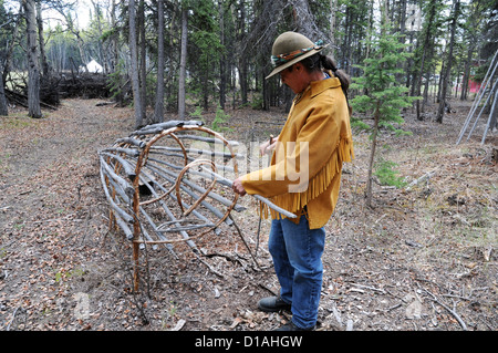 An elder of Champagne-Aishihik First Nations displays a traditional wooden salmon trap in Champagne, Yukon, Canada. - Stock Photo