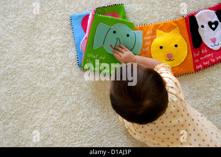 Ten months old baby playing and learning - Stock Photo