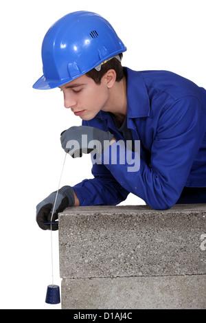 Tradesman holding a plumb line - Stock Photo