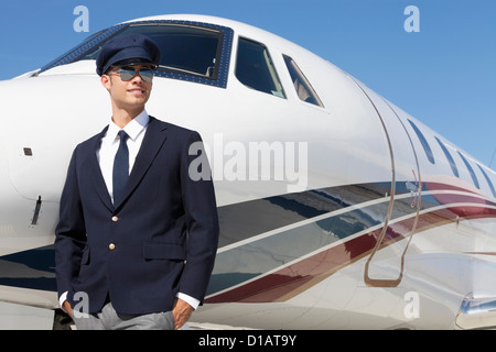 Handsome young pilot sitting by private airplane - Stock Photo