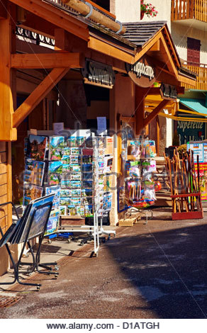 souvenir gift shop displaying racks of postcards in place de l'eglise in la clusaz france - Stock Photo