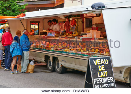 two french butchers selling meat to customers from a mobile butchers van in open air outdoor french market la clusaz - Stock Photo