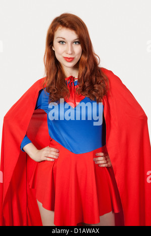 Portrait young woman in superhero costume hands on hips - Stock Photo