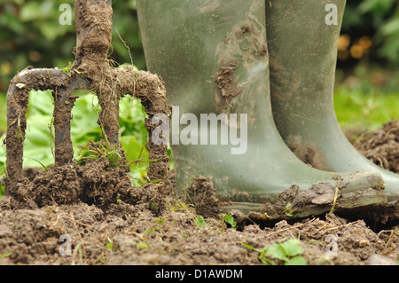 pair of boots soiled floor beside a spade - Stock Photo