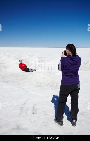 Couple taking photos on Salar de Uyuni (Salt Flats of Uyuni), Potosi Department, Bolivia - Stock Photo