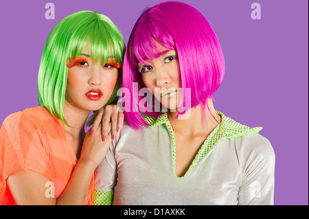 Portrait two female friends wearing wigs - Stock Photo