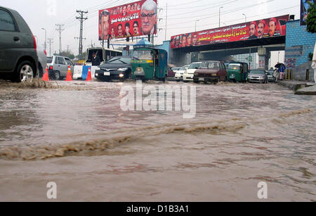 Commuters pass through stagnant rain water stand on the  road at Sooriah Bridge, in Peshawar on Thursday, December - Stock Photo