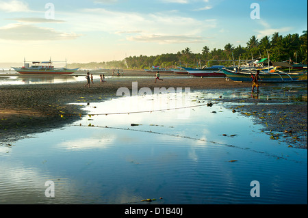 Children playing on the beach in the small Philippines village. - Stock Photo