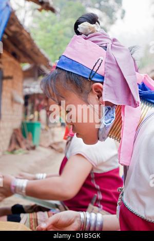 Women from the Kayan minority group working on woven fabric, Huai Seau Tao, Mae Hong Son Province, Thailand - Stock Photo