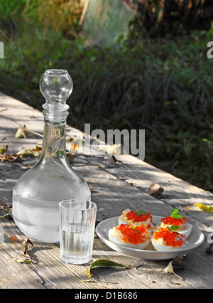Misted decanter of vodka with half full glass and boiled eggs with red caviar on the rough wooden table with shadows - Stock Photo