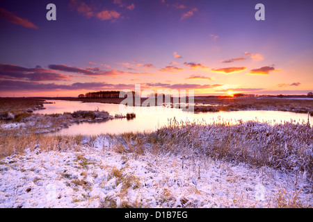 dramatic sunrise over frozen lake in winter - Stock Photo