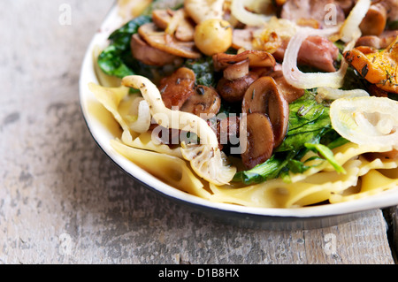 Vegetarian meal with mixed mushrooms, onion and fresh spinach on pasta. - Stock Photo