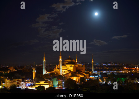 Night lights on Hagia Sophia under a clear full moon rising at night in Istanbul Turkey - Stock Photo
