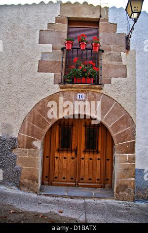 Arched wooden door and doorway, with geranium planters in the window above it, Rural Spain - Stock Photo
