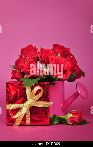 bouquet of red roses in a pink watering can with red gift box on a pink background - Stock Photo