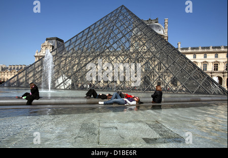 Paris, France, people bask in front of the glass pyramid at the Louvre - Stock Photo