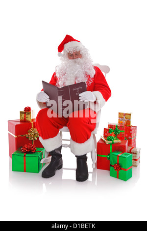 Santa Claus sat in a rocking chair surrounded by gift wrapped presents as he reads the Naught or Nice list - Stock Photo