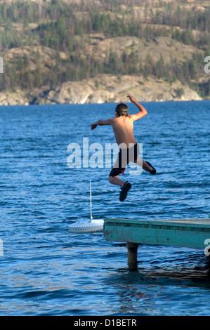 Young boy jumpng off a pier into Lake Okanogan. Outside Kelowna, BC. Canada. - Stock Photo