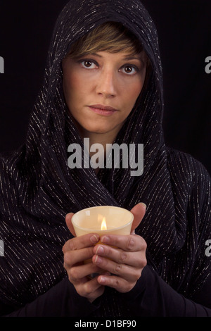 Beautiful young woman in black cape holding a burning candle in her hands and looking thoughtful at the camera. - Stock Photo