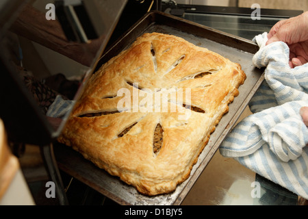 Elderly woman home baking taking a savoury pastry pie out of the oven - Stock Photo