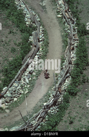 Kashmir, Sind Valley, looking down on a small child running along a village path between rough dry stone walls - Stock Photo
