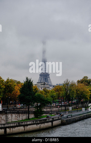 Cool and rainy day in Paris, Eiffel Tower in the fog, Seine River in the foreground - Stock Photo