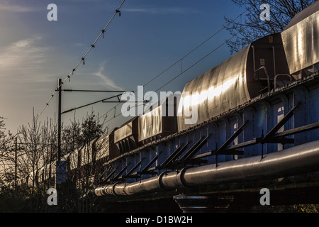 Goods train pulling out of Ely in the evening sunshine - Stock Photo