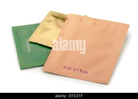 Three aluminum foil cosmetics sachets isolated on white - Stock Photo