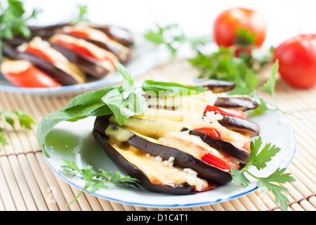 Eggplant with cheese and garlic sauce and fresh herbs, close-up - Stock Photo