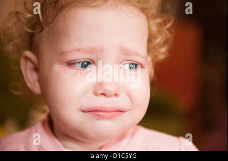 Curly haired blonde baby crying. Face closeup. - Stock Photo