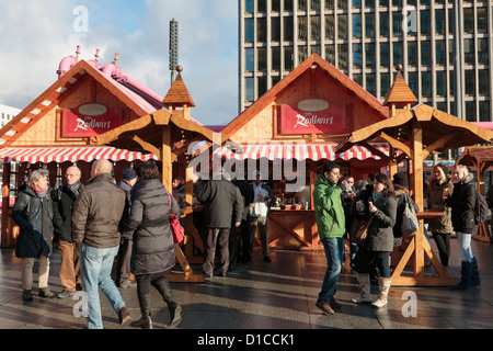 Traditional Christmas market stalls with people drinking outside in Potsdamer Platz, Berlin, Germany, Europe. - Stock Photo
