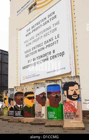 Street scene with remaining sections of the wall painted with pictures depicting a portrait of world dictators on - Stock Photo