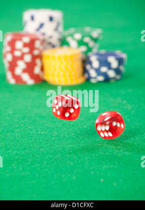 red dice on a casino table with chips - Stock Photo