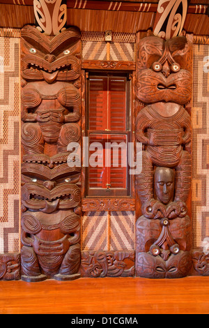 Carved Traditional Maori Figures, called Poupou, supporting the overhead rafters of the meeting house, Waitangi - Stock Photo