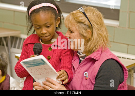 Teacher helping black female student age 5 read her classroom presentation. Expo Elementary School St Paul Minnesota - Stock Photo