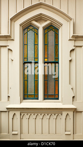Simple Stained amber Church window bordered in green on a gothic wood wall - Stock Photo