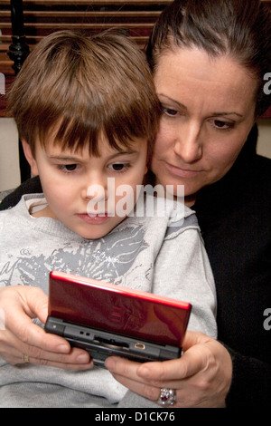 Mom and son age 40 and 5 playing a video game on his hand-held mobile electronic device. St Paul Minnesota MN USA - Stock Photo