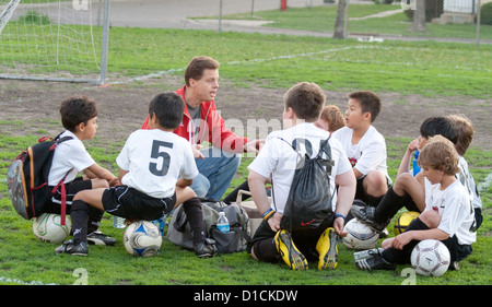 Coach discussing soccer game strategy with boys age 10 during a rest break. Monroe Memorial Park St Paul Minnesota - Stock Photo