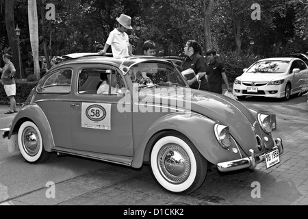 50's Volkswagen Beetle and passengers at a vintage car rally. Thailand S. E. Asia Black and white photography - Stock Photo